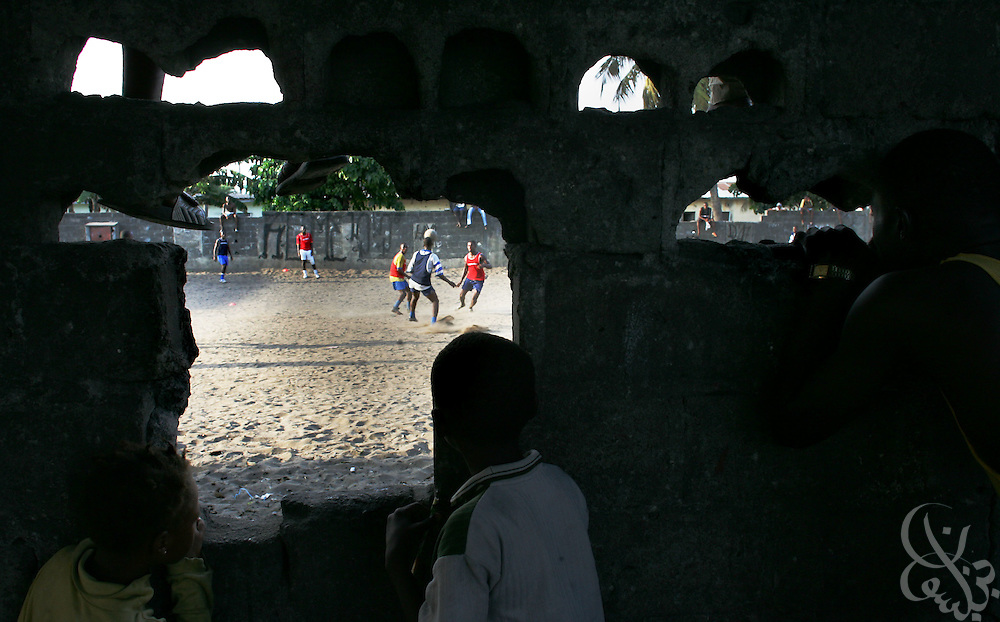 "Supporters watch through a hole in a wall as the ""Almighties of Koomassi"" academy football club practices in the Koomassi neighborhood of Abidjan, Côte d'Ivoire February 17, 2006.  Trying to mimic the successes of ASEC academy, more than 300 rival football academies have been started in Abidjan. Parents hoping of their children will become national team members or pro european league players often become indebted in order to put their children into the copycat academies, which focus on football skills, but do little to educate the young Ivorians who attend them."