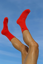 man in red socks with his legs in the air against the sky