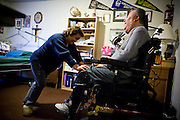 In Home Supportive Services (IHSS) caregiver Teresita Perez de Godoy, right, helps quadriplegic Francisco Godoy into his wheelchair at his Sacramento, CA home January 22, 2010. Francisco needs around-the-clock care from Teresita, his ex-wife who also lives with him. The state pays Teresita for 283 hours per month, at $10.40/hour. Gov. Schwarzenegger has proposed cutting or eliminating the IHSS program which provides care for 450,000 Californians and jobs for 375,000 caregivers. If the program was eliminated, most would need to be institutionalized, likely at far greater taxpayer expense. CREDIT: Max Whittaker for The Wall Street Journal.CABUDGET