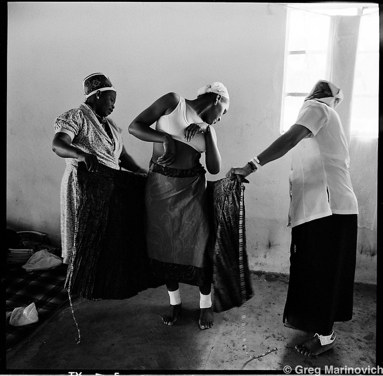 Leathle Dube, 19, is dressed by family ahead of her marriage to an older man in a mass wedding ceremony at the Nazareth Baptist Church headquarters near KwaMashu, KwaZulu Natal, January 1998. The founder Isaiah Shembe is seen as a spiritual descendent of Moses and Jesus, and th church embraces traditional Zulu values and customs. Photo Greg Marinovich
