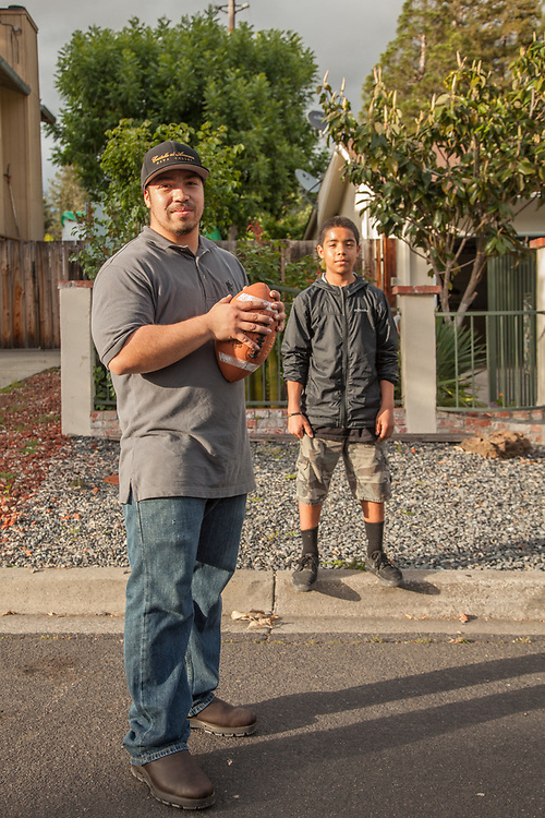 Neighbor Francisco Otero plays catch with his brother, Javier (13), in front of their house on Myrtle Street in Calistoga.