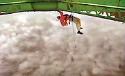 Engineer Dale Poorman dangles from a rope under the Sellwood Bridge and looks for repair issues. He is part of a team from Burgess & Niple of Columbus, Ohio. They are evaluating the span for cracks, rust, stress and holes and determined that it would need to be fully replaced in Portland, Oregon...
