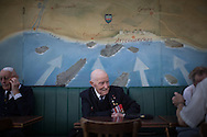 British veterans having breakfast in a coffe in Arromanches, the town where most of them landed on the 6th June 1944 as remebered by the paint on the wall