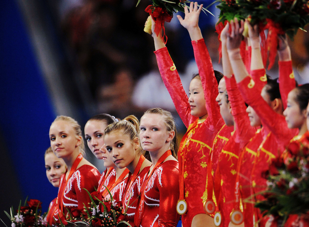 2008 OLYMPIC GAMES   - 081308 - Members of the USA gymnastics team watch as gold medal winners China take to the podium during the medal ceremony at the Olympic Games in Beijing, China. USA finished second amid questions of the ages of the Chinese gymnasts since Olympic athletes can be no younger than 16 years old.
