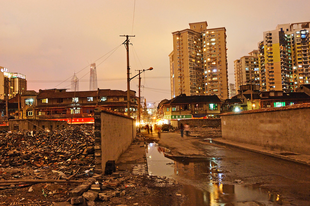 End of the old Chinese city, a street lined by walls hiding the destruction of old residential quarters cleared for new construction, whilst others survive behind. Puding skycrapers can be seen beyond at left.