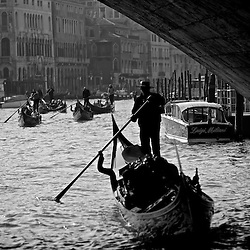 Gondolier passing under bridge Venice