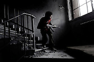 SYRIA, ALEPPO. A rebel fighter is seen as he descends the stairs avoiding to be seen by regime snipers in Bustan Al Bashar neighborhood in Aleppo . ALESSIO ROMENZI