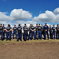 Hungarian police assembled prior to surrounding the Röszke reception centre, in an attempt to stop refugees from leaving on their own without registration. Refugees, most from Syria, simply walked through a hole in the border fence with Serbia by the hundreds on Sunday, only to be stopped by police and held in a field a kilometre away.  The official border reception centres are full and refugees must camp on the ground, dependent mostly on food donated by volunteer groups