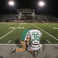 A coach consoles a football player after a playoff loss.