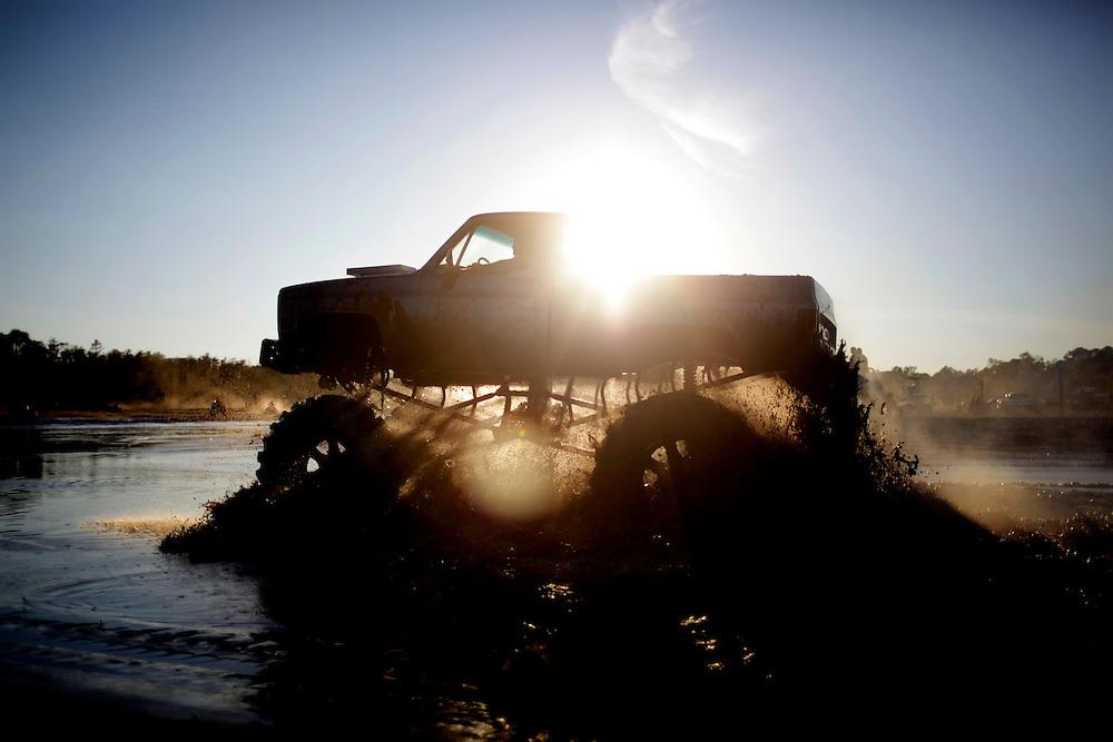 A modified truck rolls through a mud pit at the Redneck Yacht Club in Punta Gorda, Fla. Photo by: Greg Kahn
