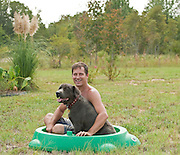 forty something man in a kiddie pool with his dog