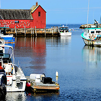 Bradley Wharf, Motif #1 and Lobster Boats in Inner Harbor of Rockport, Massachusetts<br /> Bearskin Neck in Rockport, Massachusetts, once thrived on fishing and now thrives on tourists.  This small peninsula hosts quaint shops, artisans and restaurants.  The red building with the lobster buoys is called Motif #1, an iconic symbol since 1884.  If you want to treat your taste buds, go to Roy Moore Lobster Company on the pier, order a large lobster, watch them drop it into the boiling water, and then enjoy it on the back deck.  Unbelievably good!