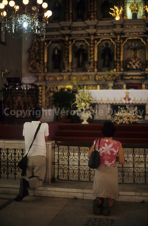 PRAYING. IN A BAROC CHURCH OF LUZON ISLAND, THE PHILIPPINES