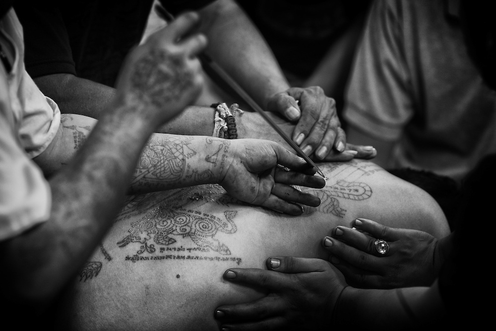 """Ajarn Harn Submomgkol, a tattoo master and Thai soldier applies a tattoo during during the annual """"Wai Kru"""" tattoo festival at Wat Bang Pra in Nakhon Chasi, Thailand Saturday, March 23, 2013.  Devotees attend the one day event to have their """"Sak Yant"""" religious tattoos energized by Buddhist monks and tattoo masters."""