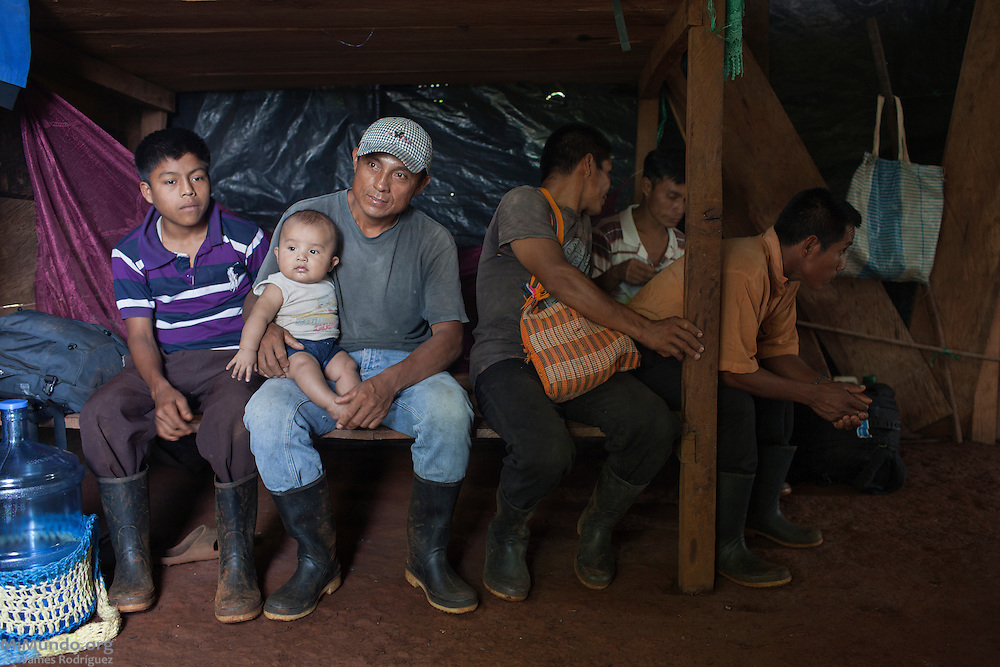 Isaac Coc Coc (middle), 36, sits on a bed with his 5-month-old son Hernan Ismael among other community members of Lote 8. Isaac is the husband of Carmelina Caal Ical, 28, one of the eleven plaintiffs in the Caal vs. HudBay legal case in Canada. The Q'eqchi' Mayan community of Lote 8 was violently evicted on January 17, 2007, by State forces at the orders of the Guatemalan Nickel Company (CGN), then-owned by Canadian mining firm Skye Resources. During the eviction, numerous local women were gang-raped by Police officers and CGN security personnel. In a landmark legal case, eleven women from Lote 8 are suing HudBay Minerals Inc., the mining firm that purchased Skye in 2008, in the home jurisdiction of Ontario, Canada, for negligence and carelessness causing physical and psychological harm. Lote 8, El Estor, Izabal, Guatemala. May 19, 2014.