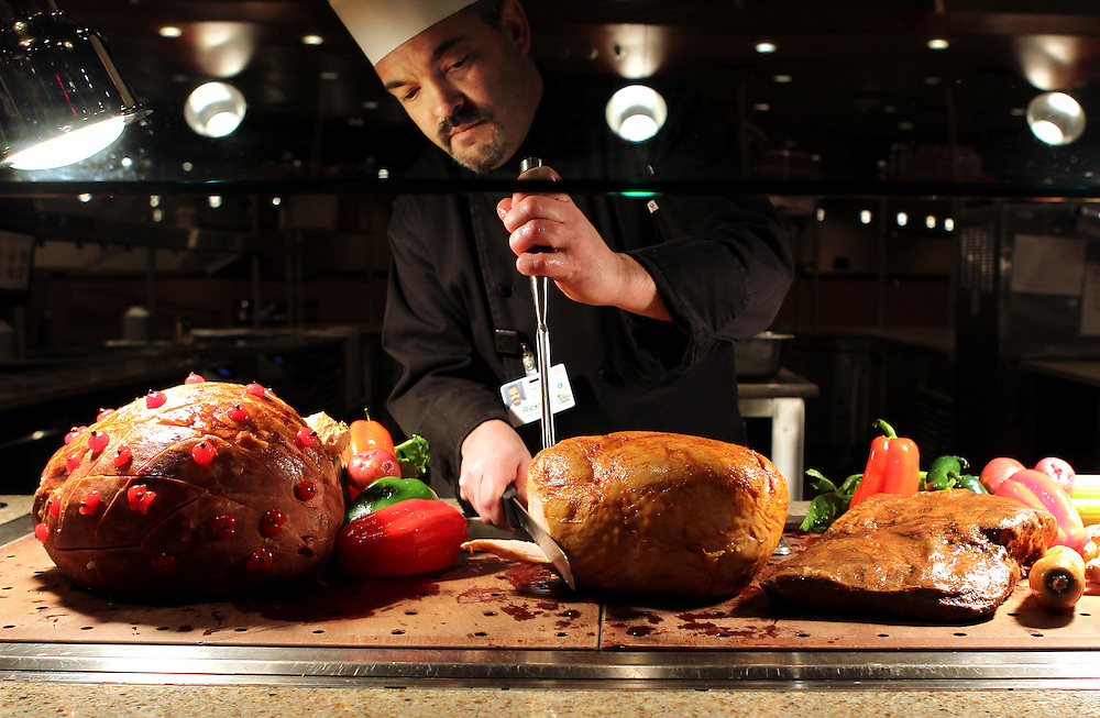 Buffet Kitchen Manager Ricky Bouley slices slow-roasted turkey at the carving station in the Grand Buffet at Grand Casino Hinckley December 20, 2011.