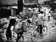 Exported toxic waste: Children ride past computer components, which contain toxic heavy metals, brought in from North America, Europe and Japan to be dismantled to obtain recyclable materials to sell in what was, less than a generation ago, a bucolic agricultural village.  Near Guiyu, Guangdong, China.