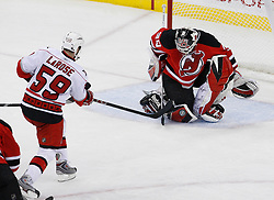 Apr 23, 2009; Newark, NJ, USA; New Jersey Devils goalie Martin Brodeur (30) makes a save on a shot by Carolina Hurricanes right wing Chad LaRose (59) during the third period of game five of the eastern conference quarterfinals of the 2009 Stanley Cup playoffs at the Prudential Center. The Devils beat the Hurricanes 1-0 to take a 3-2 lead in the best of 7 series.