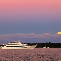 A motor yacht with a deck full of passengers cruises through Miami harbor towards southern Biscayne Bay and the Atlantic Ocean, as the full moon rises over Virginia Key in the background.