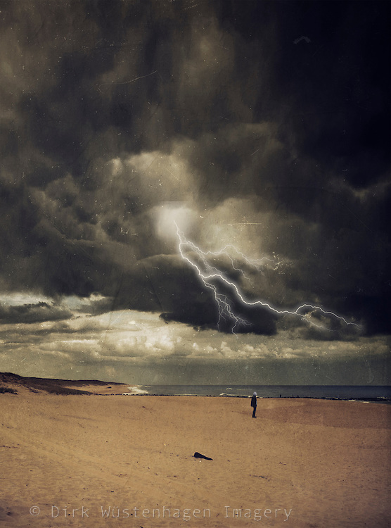 Man standing on a beach under a dark sky with a lightning flash<br />