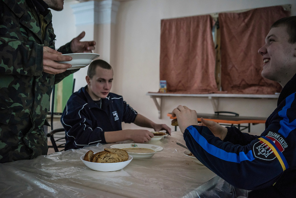 Security guards eat lunch in a communal dining hall at Romashka, a summer camp where they and several hundred other people live after being displaced by fighting in Eastern Ukraine on Friday, February 13, 2015 in Kharkiv, Ukraine.