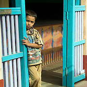 Boy at entrance to his home in Thittacheri.Balustrade in Blue.