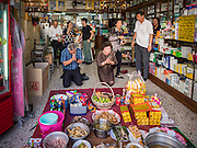 27 JANUARY 2017 - BANGKOK, THAILAND: A Thai-Chinese family sets the family Chinese New Year meal in their pharmacy shop in Bangkok. 2017 is the Year of the Rooster in the Chinese zodiac. This year's Lunar New Year festivities in Bangkok were toned down because many people are still mourning the death Bhumibol Adulyadej, the Late King of Thailand, who died on Oct 13, 2016. Chinese New Year is widely celebrated in Thailand, because ethnic Chinese are about 15% of the Thai population.     PHOTO BY JACK KURTZ
