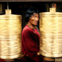 Tibetan Buddhist saying his mantra silently while turning the prayer wheels of the Jokhang monastery in Lhasa.