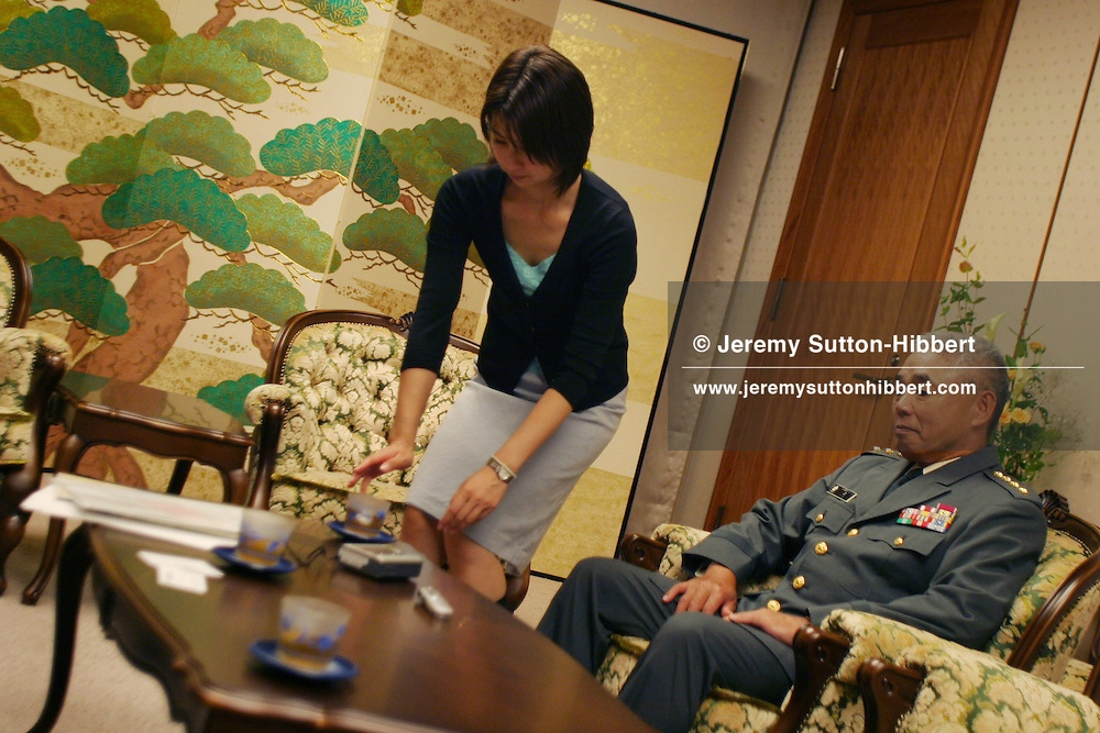 An employee of the Japan Defence Agency brings General Tsutomu Mori, of Japan Self Defence Force ground troops, a cup of tea during an interview,in  Tokyo, Japan on Tuesday, Sept. 27th 2005. During interviews it is common for female assistants to enter the rooms silently , bringing refreshment drinks of green tea, coffee, or orange juice, to the company head and his guests.