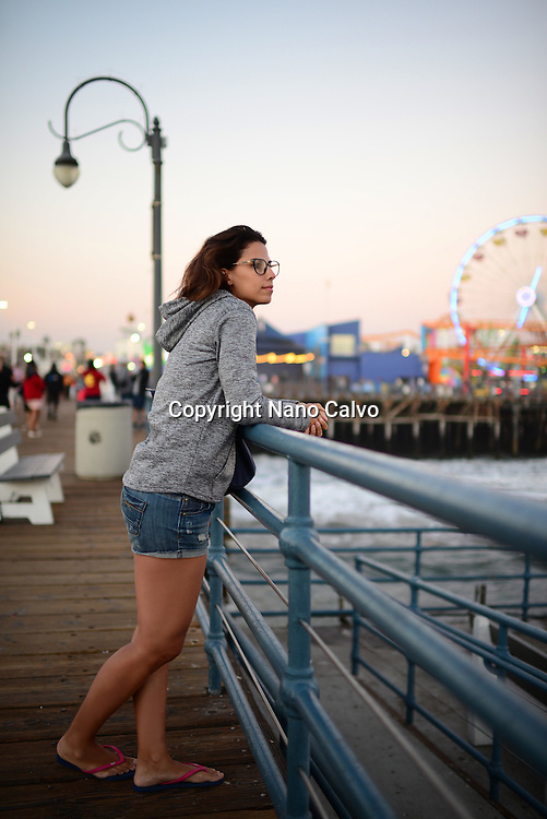 Attractive young woman relaxing in Santa Monica pier, California.
