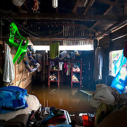 Three families live in this crowded house, every week they are forced to move their possessions higher and higher to avoid the rising water. Image © Jonah Markowitz/Falcon Photo Agency