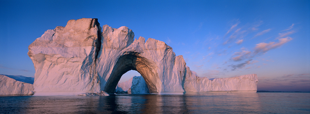Greenland, Ilulissat, Setting sun lights massive arched iceberg from Ilulissat Kangerlua Glacier (Jakobshavn Icefjord) floating on calm seas in Disko Bay along western coastline