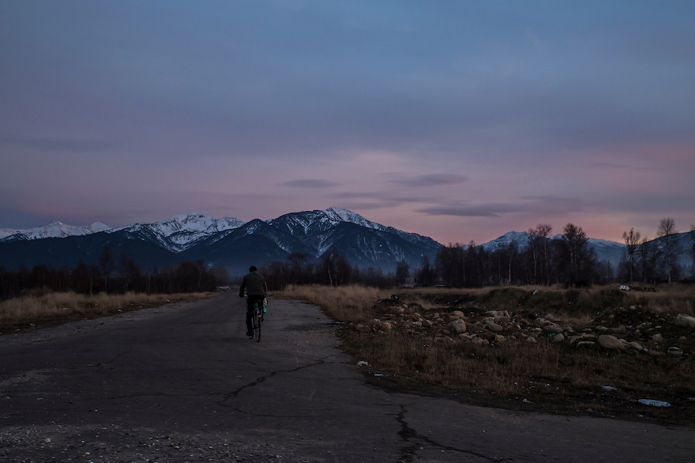 A man rides his bicycle down a road at the edge of town on Wednesday, October 23, 2013 in Vydrino, Russia.