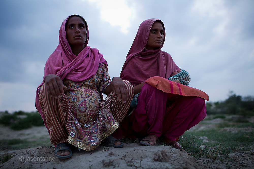 Saphia bibi (left), 25 years of age and 9 months pregnant sits with her cousin Sumia, also 25 years of age. Both women were forced to evacuate their home in the middle of the night when floodwater swept through the village of Shlar in the district of Muzzafargarh...Both women left 12 days ago, accompanied by their husbands they took 2 days to reach a friends house some 12km away on higher ground away from the encroaching waters edge. ..They had no time to collect belongings, they have no money, no ID Card, no clothing or furniture...They survive of donations of one traditional nan bread, each, per day and have no access to clean drinking water.