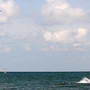 Para skiing in the Caribbean with Hobie cat sail boat in the distance.