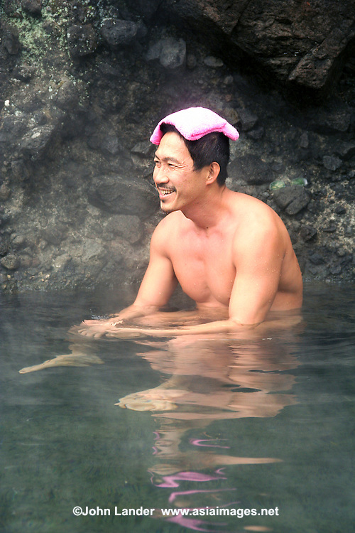 "A Japanese man relaxing at an open air hot spring called a ""rotemburo"" in Japan.  Bathing in a natural atmosphere, among the trees and under open skies is a favorite with Japanese.  Nowadays it is almost a requirement for any hot spring resort to have outdoor baths thanks to their popularity."