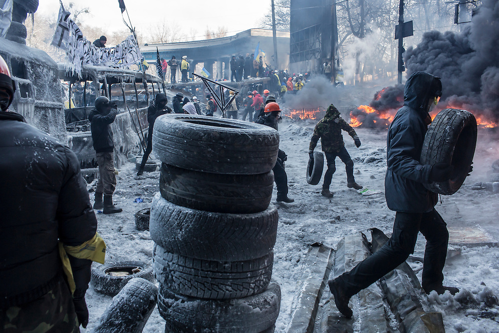 KIEV, UKRAINE - JANUARY 25: Anti-government protesters burn tires during clashes with police on Hrushevskoho Street near Dynamo stadium on January 25, 2014 in Kiev, Ukraine. After two months of primarily peaceful anti-government protests in the city center, new laws meant to end the protest movement have sparked violent clashes in recent days. (Photo by Brendan Hoffman/Getty Images)