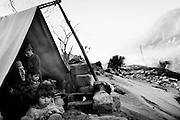 A grandmother with her grandchildren on the outskirts of Balakot. A tarpaulin stretched over a post is their cold and windy home on the roof of the town&rsquo;s collapsed hotel. <br /> Balakot - Nov. 2005