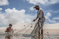 Aldemir Brito, 39, fishing with his son Adriel, 13, in one of the lagoons close to his house in Queimada dos Britos. The knowledge of living in the dunes is passed from father to son for generations. They live of fishing in the sea, which is two hours away. In the winter they breed fish on the lagoons, and cattle and goats that run free on the dunes. They have a small garden for farming but nothing major since they are afraid of the accelerating advance of the dunes that have already covered several houses. No one really knows when the village was founded but the legend says that the founder Manuel Brito, when running away from home due to a drought that was scorching his homeland, he ended up settling down in the only non-sandy portion of the Lençois.