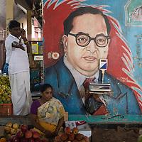 Fruit vendor under a political poster, Koyambedu Fruit Market, Chennai, Tamil Nadu, India