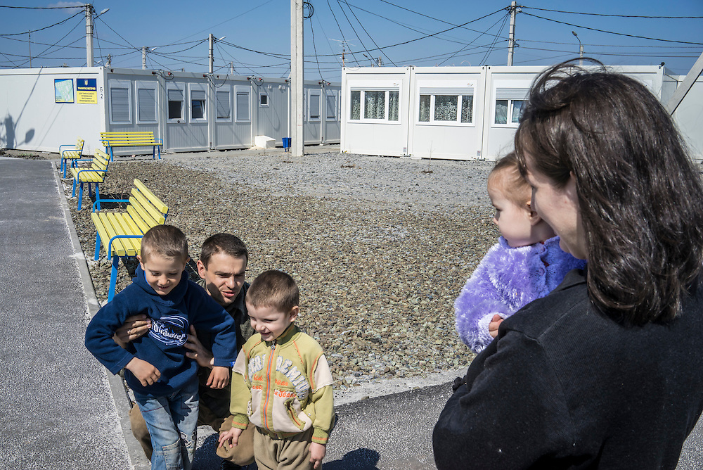 Aleksandr Ortinsky, 35, with his wife and three of his six children, originally from Lugansk, amid a cluster of prefabricated container houses known as Transit City on Monday, April 27, 2015 in Kharkiv, Ukraine. They now live there as one of 83 families, and 387 people total, who are IDPs forced to flee eastern Ukraine because of fighting between Ukrainian forces and pro-Russian rebels. CREDIT: Brendan Hoffman/Prime for the Wall Street Journal UKRMIGRATION