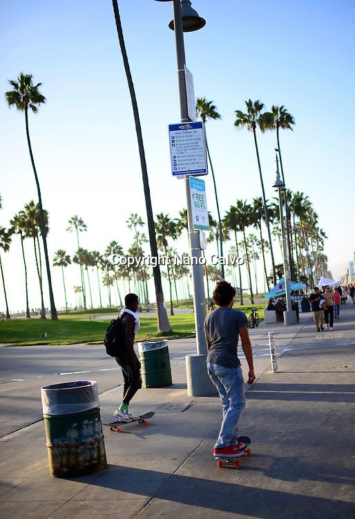 Young skaters in Venice Beach boardwalk, California.