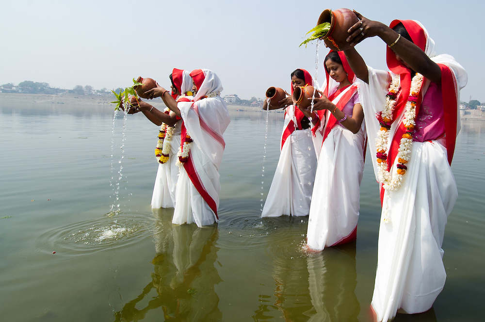 Hindu women bow in prayer and perform religious rituals in gratitude to river Ganga held sacred by followers of Hinduism. Millions of Hindus bathe in the river daily if living close, or annually at special holy places (tirthas). Many cast the ashes of their dead into its waters, and cremation temples are found along its banks in many (pilgrimage) places.