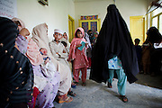 Mostly women and children await consultations in the waiting area of Qambar Clinic...Qambar Clinic on the outskirts of Mingora in the SWAT Valley is supported by Save the Children. The resident medical doctor is Dr Ikram who was the first Doctor to return to the clinic since the Taliban were driven out by government forces in 2009...Dr Ikram sees approx. 50 people per day with flooding/water related illnesses and symptoms such as diarrhoea, vomiting, high fever, dysentery, dehydration, skin diseases and upper respiratory infections...Dr Ikrams medical opinion is that many of the illnesses are related to ice. During the hot weather, families and children in particular buy ice to cool don in the hot climate, however, it is suspected that the water used to produce the ice is drawn from contaminated sources...The majority of the children seen are between the ages of 2-10 years of age. At the moment the clinic estimates it is receiving 1-2 cases per day of suspected Malaria, but without an in house testing laboratory, they cant confirm suspected cases of Malaria or Cholera. Due to the increase in patients attending the clinic as a result of the flooding, they are now running short on some medicines...Patients prefer to visit this Save the Children sponsored clinic over the government hospitals as they trust the NGO employed doctors more than those employed by the government, and medicines will be more readily available and the NGO clinic...The clinic offers free medical consultations, medicines and free hygiene kits. During the flooding, the clinic has operated a 7 day week, from 8am until 14.00pm..