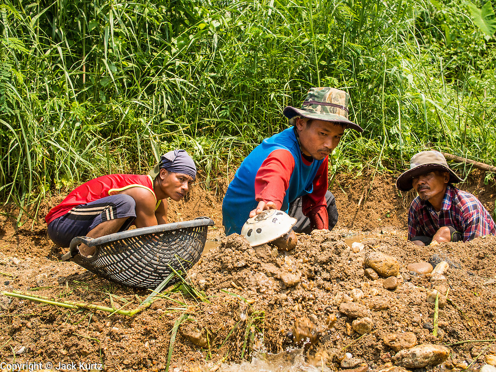 """22 APRIL 2014 - WANG NUA, LAMPANG, THAILAND: Artisanal gold miners dig a new mine on the banks of Mae Wang. Villagers in the Wang Nua district of Lampang province found gold in the Mae Wang (Wang River) in 2011 after excavation crews dug out sand for a construction project. A subsequent Thai government survey of the river showed """"a fair amount of gold ore,"""" but not enough gold to justify commercial mining. Now every year when the river level drops farmers from the district come to the river to pan for gold. Some have been able to add to their family income by 2,000 to 3,000 Baht (about $65 to $100 US) every month. The gold miners work the river bed starting in mid-February and finish up  by mid-May depending on the weather. They stop panning when the river level rises from the rains. This year the Thai government is predicting a serious drought which may allow miners to work longer into the summer.    PHOTO BY JACK KURTZ"""