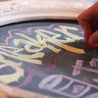 Artist Kyle Page draws a sign in chalk during Sneaker Jam Sunday July 20, 2014 at Carolina Club 1880 in Wilmington, N.C. The event offered sneaker collectors the opportunity to purchase and trade new and rare shoes. (Jason A. Frizzelle)