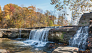 Upper Falls, in Cataract Falls State Recreation Area –  Indiana's largest-volume waterfall. Mill Creek plunges 20 feet in the set of Upper Falls, and a half a mile downstream the Lower Falls drops 18 feet, for a total drop of 86 feet including intermediate cascades. Autumn foliage colors were brilliant but water volume was low for this photo in mid October 2015. The park's limestone outcroppings formed millions of years ago when the region was covered by a large shallow ocean. Cataract Falls State Recreation Area is an hour southwest of Indianapolis, near Cloverdale, Indiana, USA. This panorama was stitched from 2 overlapping photos.