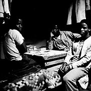 Youthful migrant workers in their shared dormitory, Mamelodi hostel, Mamelodi, Pretoria, 1989. Scanned from original polaroid. Greg Marinovich