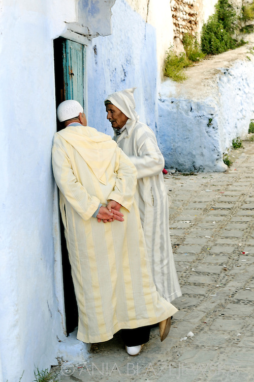 Morocco, Chefchaouen. Men chatting at the opened door.
