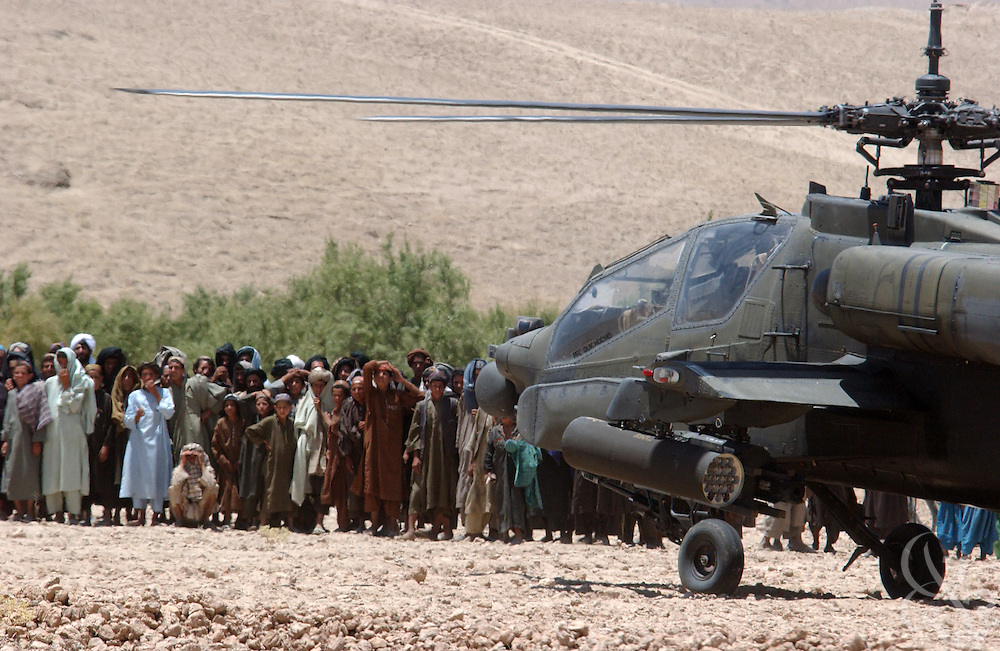 Local Afghans gather around a U.S. Army Apache helicopter during the July 7, 2002 visit by U.S. Army Gen. Dan McNeill, commander of the Coalition Joint Task Force (CJTF 180), to Deh Rawud in Southern Afghanistan. McNeill used the visit to speak with local leaders about the possibility of stationing more U.S. troops in the region, following an incident last week in which U.S. aircraft mistakenly targeted Afghan civilians celebrating in the village.